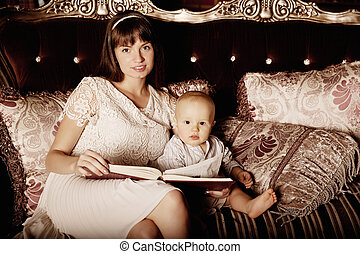 Mother with a small child in the interior reading a book...