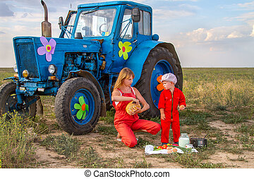 mother feeding her son tractor in a field near the tractor -...