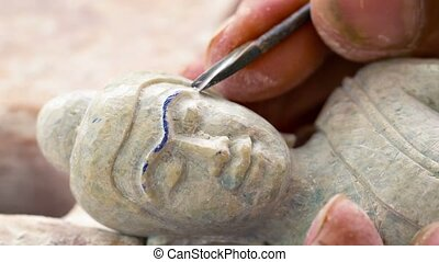 Master carves a sculpture of Buddha. Stone-cutting workshop...