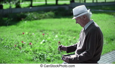Technological Maturity - Senior man sitting in park and...