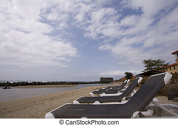 Beach chairs in the sand in a topical resort