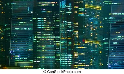 Night windows of office buildings in a big city. Singapore -...