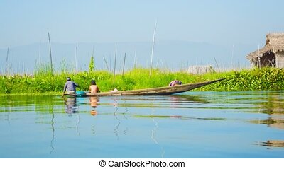 Locals on a boat near the floating vegetable garden Burma,...