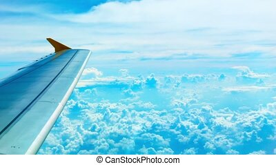 Bright view of the clouds and the wing from the aircraft cabin
