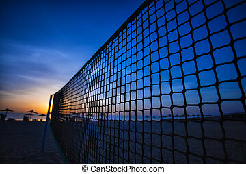 volleyball net and sunrise on the beach - Sillhouette of a...