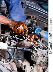 mechanic fixing car - a mechanic fixing the car under the...