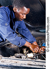 african mechanic - an african mechanic repairing a vehicle