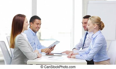 smiling team with tablet pc working in office - business,...