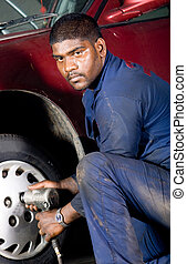 mechanic changing tyre - a mechanic removing the wheel of a...