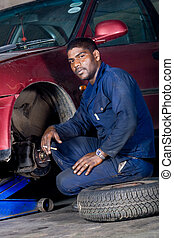 mechanic changing wheel - a mechanic changing the wheel of a...