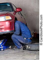 man workin gunder vehicle