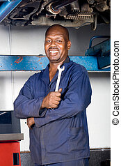kind african mechanic - a kind african mechanic posing with...