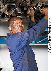 african mechanic working - an african mechanic working under...