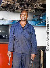 working mechanic - a working mechanic posing in workshop