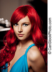 Young woman with luxurious long beautiful red hair in a blue fas
