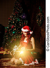 Young beautiful smiling santa woman near the Christmas tree...