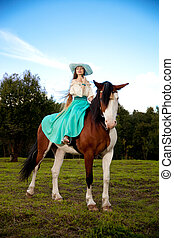 Beautiful woman with a horse in the field. Girl on a farm...