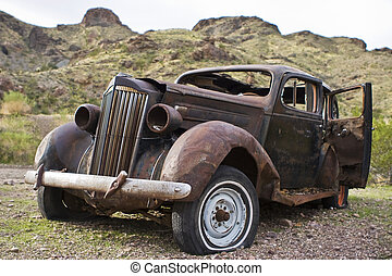 Rusted Abandoned Car in Desert - Old rusted abandoned car in...