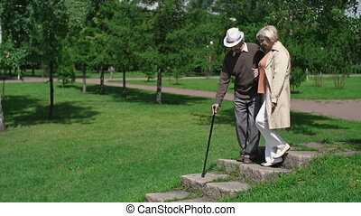 Decline of Life - Senior couple stepping down the hill along...