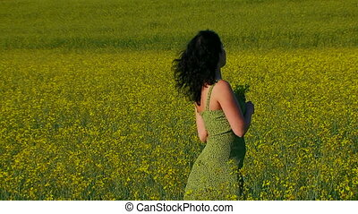 Beautiful lady in green dress is posing on the field of Raps.