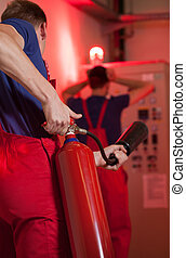 Man using fire extinguisher in factory, vertical