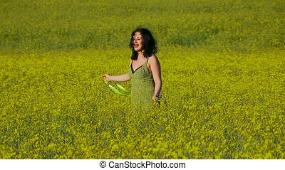 Lovely lady in green sun-dress walks on the field of Raps.