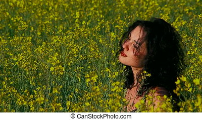 Ecology Thoughtful woman is in a field of Raps - Wind is...