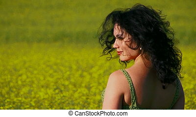 Ecology. Curly woman is sitting in a field of Raps.