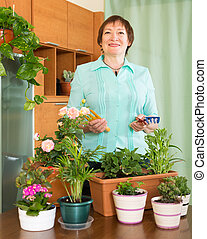 Mature woman with plants at home