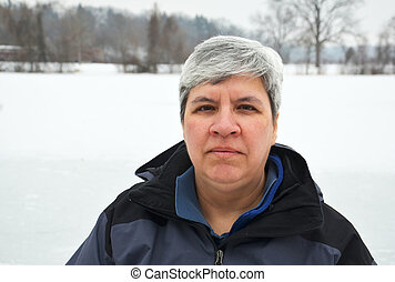 Middle aged woman looking at camera, winter background