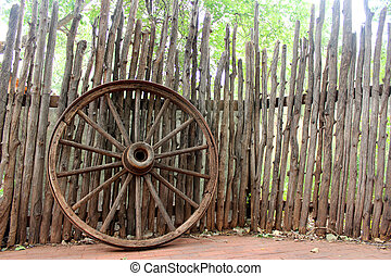 Vintage wagon wheel and log fence