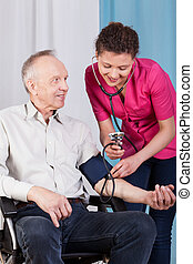 Nurse measuring blood pressure of disabled man