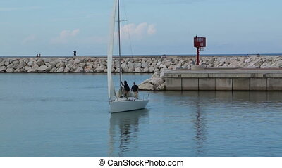 Sailing boat sails to the pier. The sailors lowered white...