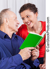 Grandfather and granddaughter reading book - Closeup of...