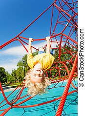 Smiling boy hangs upside down on rope of red net - Smiling...