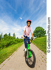 African boy in red helmet rides bright green bike along the...