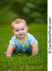 Summer portrait of happy baby boy infant outdoors at park