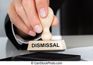 Hand Holding Rubber Stamp With Dismissal Sign - Closeup of...
