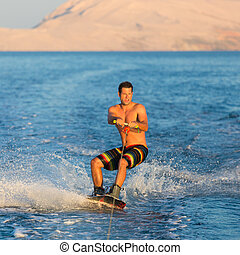 Wakeboarder in sunset. - Wakeboarder in colorful shorts...