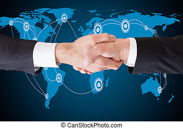 Businessmen Shaking Hands Against World Map - Cropped image...