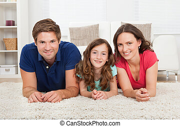 Family Lying On Rug At Home - Portrait of smiling family...