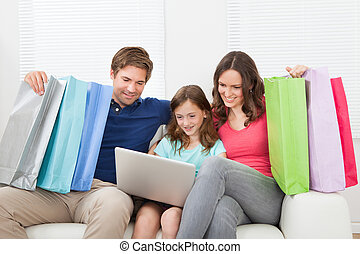 Family Of With Shopping Bags Using Laptop - Happy family...