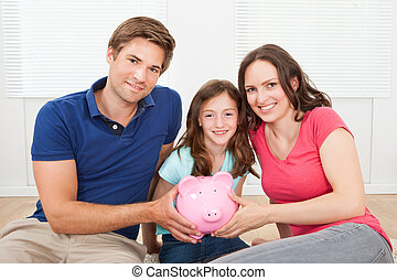 Happy Family Holding Piggy Bank At Home - Portrait of happy...