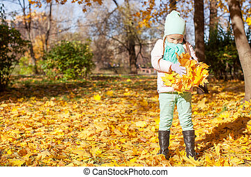 Little cute girl on the autumn meadow in a sunny fall day