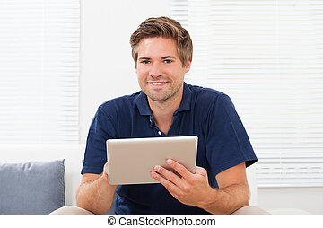 Man Using Digital Tablet On Sofa At Home