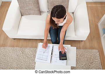 Confident Woman Calculating Home Finances At Table -...