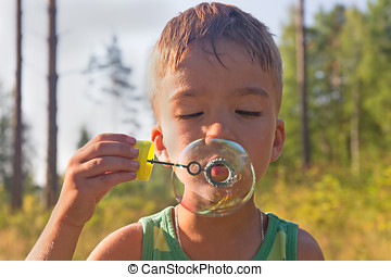 boy and soap bubbles - Portrait of the boy inflating soap...