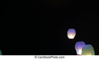 bride and groom lit a Chinese lantern on the beach