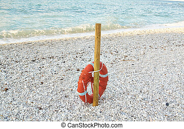 Red lifebuoy attached to pole on the beach in summer