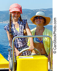 Mother with her daughter in a motorboat. - Mother with her...
